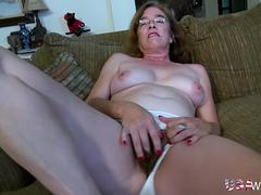 Mature slut stripping down and masturbate naked on a couch