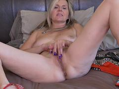 Naughty mature lady rubs her pussy on the bed