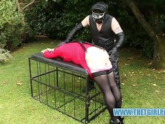 Redhead TGirl slut handcuffed spanked and whipped in the garden by leather clad master